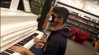 Un jeune homme joue du piano les yeux bandés