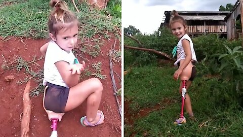Little girl with only one leg triumphantly climbs hill