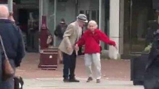 Un couple âgé et amoureux danse en pleine rue