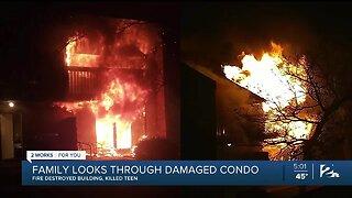 Family looks through damaged condo