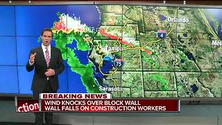 Wind knocks block wall onto construction workers
