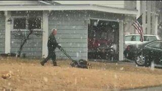 Man mows his lawn during snowstorm