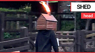 Just a man walking along the street with a flame-throwing shed on his head
