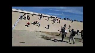 Migrants run through canal toward border