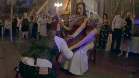 Good sport groom laughs at wedding garter toss trickery