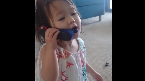 """Toddler on """"cell phone"""" is deep in conversation"""
