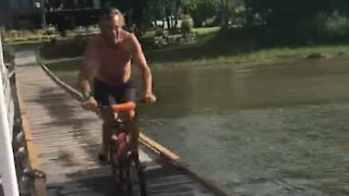 Guy performs epic lakeside bicycle jump