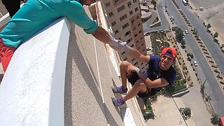 Heart-stopping moment daredevil lets go of his friend's hand while hanging off a building – before grabbing on again