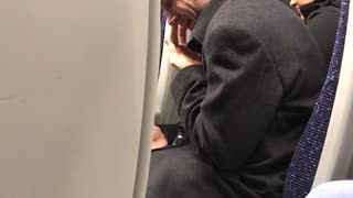Man black sweater picking nose on train secretly