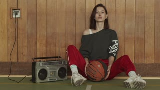 A Woman Sitting While Dribbling a Ball Beside a Radio