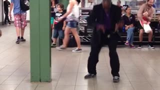 Man in black and purple suit dances crazily to a piano song in a subway station