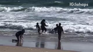Man carries white mattress on beach