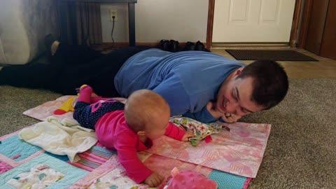 Adorable baby girl laughs at dad crawling