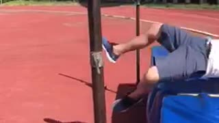 Guyrunning on track field tries to jump over pole fails
