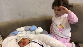 Baby girl adorably takes care of her little brother