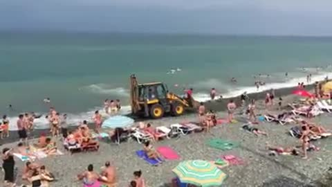 The tractor is doing the job on the beach