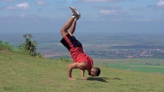 Man Doing Handstand in Grass Field