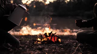 People pouring a warm drink around a campfire