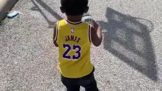 Watch this toddler drill a long distance basketball shot with ease
