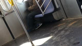 Man lights up a cigarette inside subway train