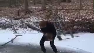 Guy drops giant rock on frozen lake falls