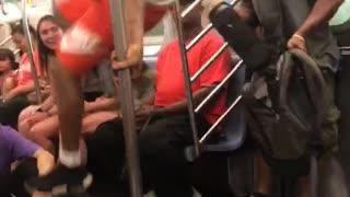 Guy white shirt red shorts dancing hanging subway train
