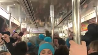 Subway train filled with college students wearing gray and blue beanie singing song