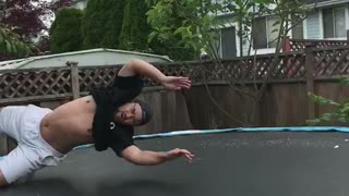 Guy tries to backflip in trampoline and lands on head, holds head in shame