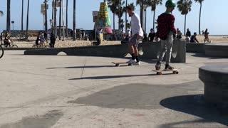 Kid in white shirt near beach skateboard