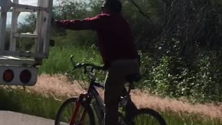 Bicycle Rider Holds onto Truck Tailgate