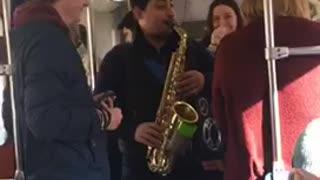 Guy playing saxophone on subway train