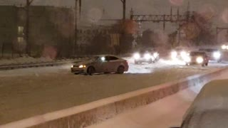 Car Does Donuts on Highway During Snowstorm