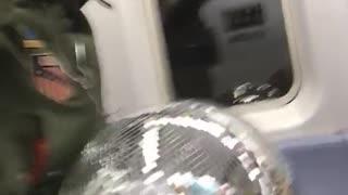 Guy holds giant disco ball on subway train