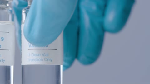 Sliding Extreme Close Up Shot of Covid Vaccine Vials As Hand Takes One Away