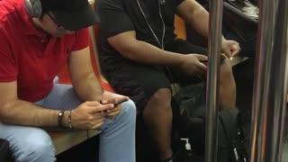 Guy white headphones dancing on subway seat black clothes