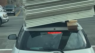 Building Supplies Barely Balanced on Car Roof