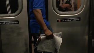 Man in a blue shirt standing between train doors