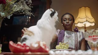A Woman Petting Her Cat On The Dining Table