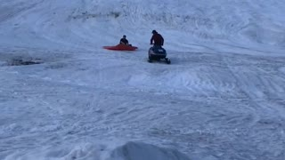 Snowmobile Plunges Passenger into Pond