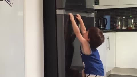 Cute spider man toddle try to climb the fridge