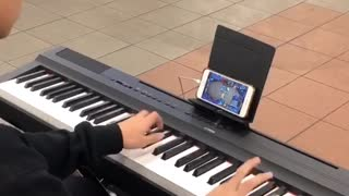 Kid playing piano while playing game on phone