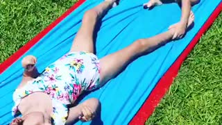 Toddler helps big sister with Cerebral Palsy down water slide