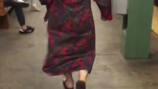 Bald person red headphones bathrobe walking subway platform station