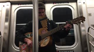 Guy plays guitar and pan flute on subway train