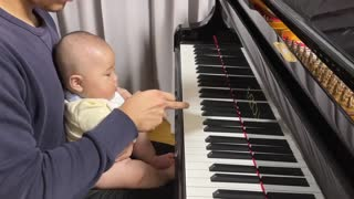 A baby who uses his dad's super-luxury piano as a toy