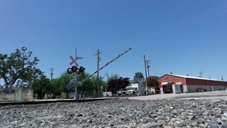 A Train Passing Through A Railroad Crossing