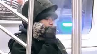 Woman smokes on subway train