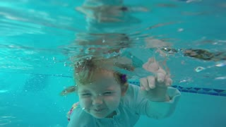 Skilled baby jumps in pool, floats on her own