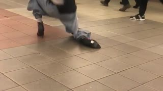 Man in heals and black shirt dancing subway station
