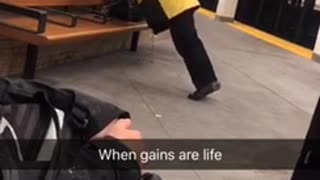 Man does semi-pushups off of a seat in a subway station
